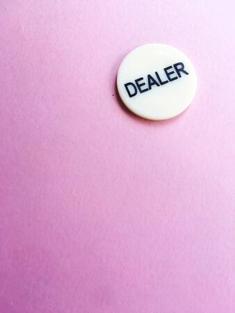 Chip dealer lies on a pink background. The game of poker. Place for text. Gambling. Concept.