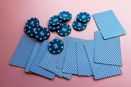Poker chips and cards on a pink background. The game of poker. Chip dealer. Gambling.