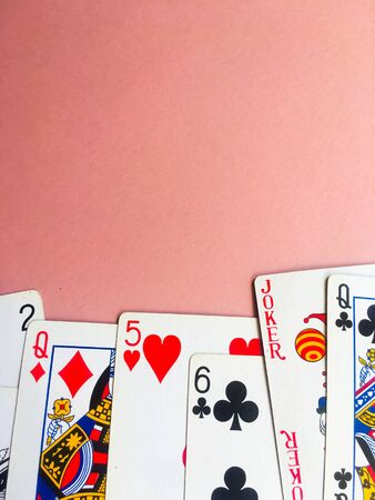 Cards for playing poker lie at the bottom of a pink background. Place for text. Gambling.
