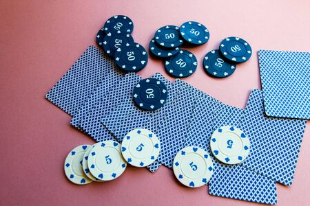 Poker chips and cards on a pink background. The game of poker. Chip dealer. Gambling