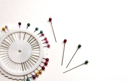 Set of sewing needles with colored beads in an organizer on a white isolated background. Copy space.