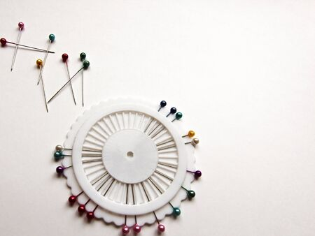 Set of sewing pins with colored beads in an white organizer on a white isolated background