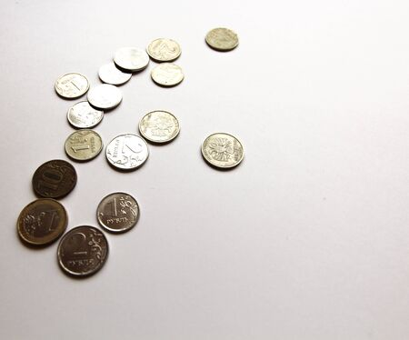 Several Russian coins lie on a white isolated background. Shiny Russian metal money.