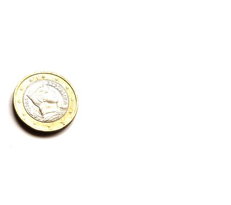 A metal coin of 1 euro lies on a white background. European money. Place for text.