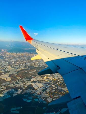 The view from the airplane window on the city. From the window you can see the wing of the aircraft