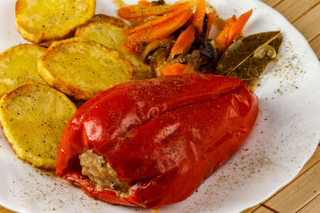 Stuffed peppers and fried potatoes with vegetables.