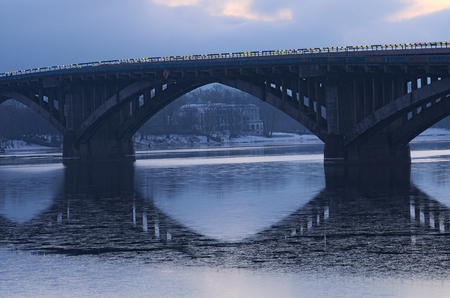 Frosty early morning. Metro bridge reflected in the water. On the other side you can see the white building. Kyiv. Ukraine. Stock Photo
