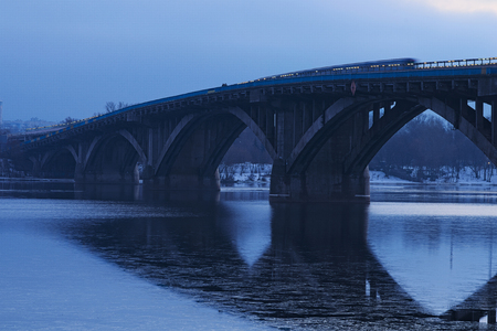 Frosty early morning. Metro bridge reflected in the water. The first metro train moves on the bridge. Kyiv. Ukraine.