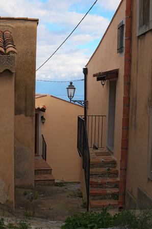 Narrow pedestrian street. You can see Tyrrhenian Sea in the background. Tindari. Sicily. Banco de Imagens