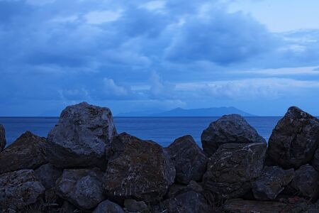 patti: Large stones are designed to protect the coastline from the large waves. Islands can be seen on the horizon. Marina di Patti. Sicily.