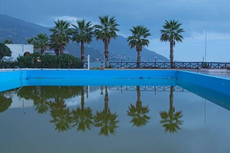 아름 다운 야자수 수영장 근처입니다. 산 근처의 건물을 볼 수 있습니다. 마리나 디 패티. 시칠리아.