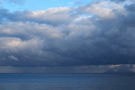 patti: Storm clouds are low over the sea. Mountains in the haze could be seen on the horizon. Marina di Patti. Sicily.