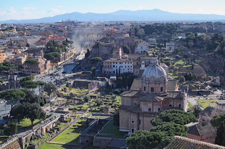 ROME, ITALY - JANUARY 6, 2017: View to rooftops of Rome skyline from the Monument of Vittorio Emanuele at Piazza Venezia. Rome Forum with ruins of historical buildings. Colosseum in the background. Winter morning view.