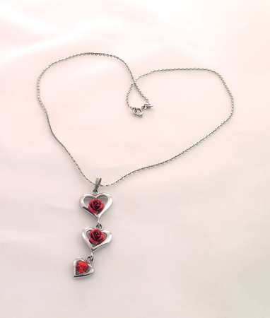 Silver chain and pendant with hearts, red roses and crystal. Lying in the form of heart on light background. photo