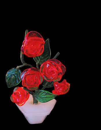 The figurine from a glass represents a bush of red roses. It is isolated on a black background. photo