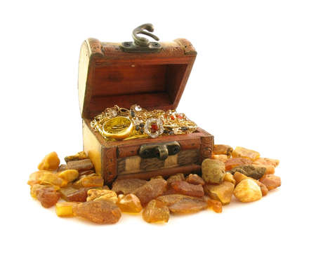 big bin: Jewelry in wooden chest and amber round it. It is isolated on a white background.