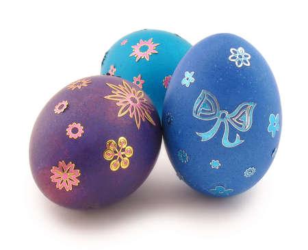 azul turqueza: Tres huevos de Pascua (azul, turquesa, violeta) con ornamentos. Est� aislada sobre fondo blanco.