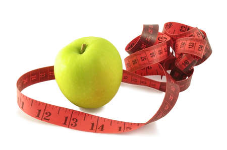 centimetres: Green apple and pink measuring tape (centimetres and inches). It is isolated on white background.