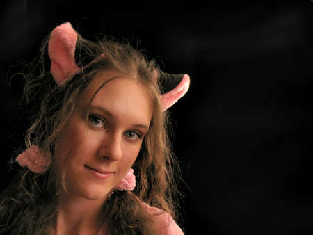 Portrait of a cute girl with toy cat ears on her head. Primary colors: black and pink, black background. Stock Photo - 10460478