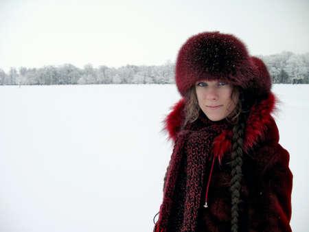Portret van mooie meisje met lange vlechten op de achtergrond van een winterlandschap.