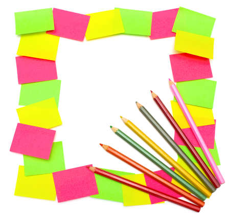 Colorful reminders  frame from paper stickers  green, yellow, pink  and seven colored pencils isolated on white background  photo