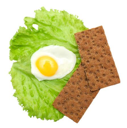 huevos estrellados: Comida sana: huevos fritos, lechuga, pan crujiente aislados en blanco