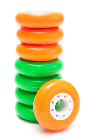 rollerskates: Orange and green inline rollerskates wheels isolated over white