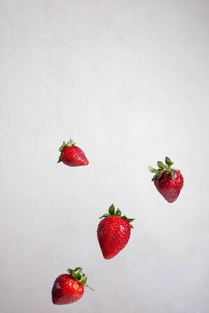 red strawberries tossed in the air