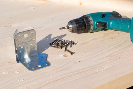 electric screwdriver, corners and screws on the boards of the timber with sawdust