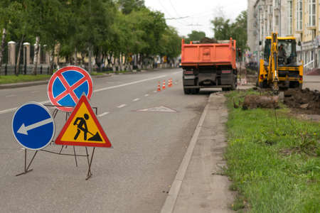Road signs, detour, road repair on street background, truck and excavator