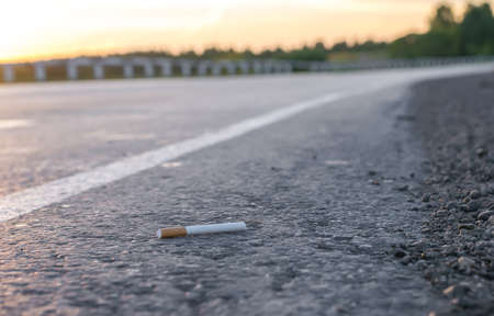 View of cigarette lying on the asphalt on a country road in the evening