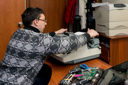 A guy prints documents on mechanical typewriter Stock fotó