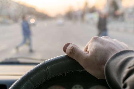 man's hand on the steering wheel