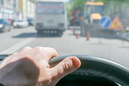 Driver hand in the steering wheel