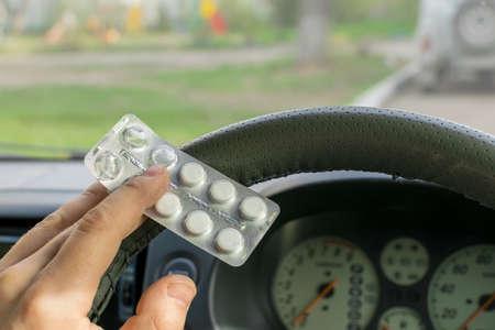 Driver hand holds a pills