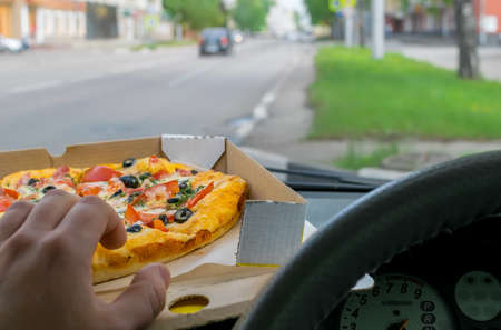 driver eats pizza in the car Stock Photo