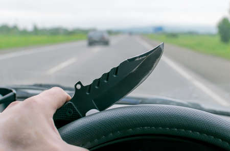 Crime, man, driving a car holding a knife