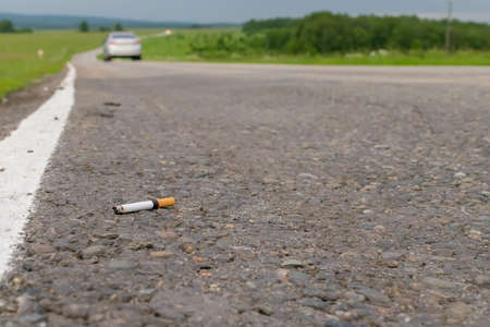 View of cigarette lying on the asphalt