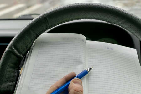 driver holds a paper notebook and makes notes