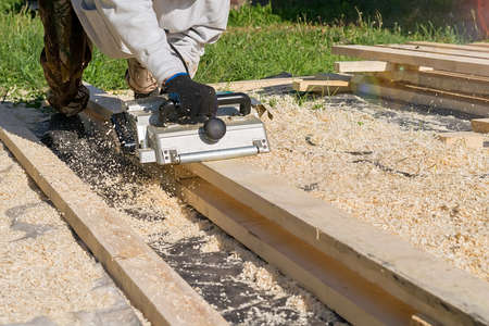 man planing boards with electric tools