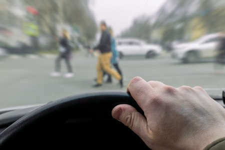 a man's hand on the steering wheel of a car while braking at a pedestrian crossing