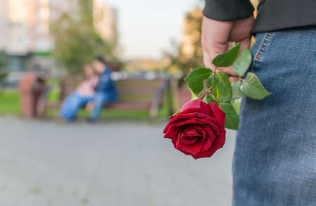 view of a man with a rose flower on the background of a couple sitting on a bench in the Park Foto de archivo - 138469352