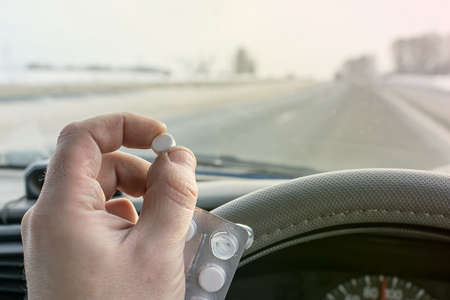 View of the driver hand holding a bag of pills