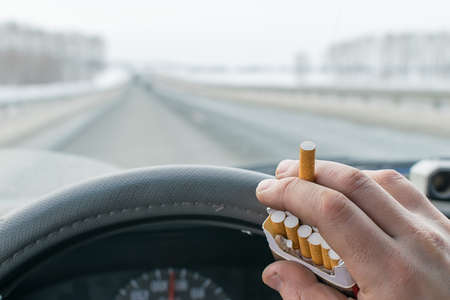 View of a car driver hand holding a pack of cigarettes while driving on the highway