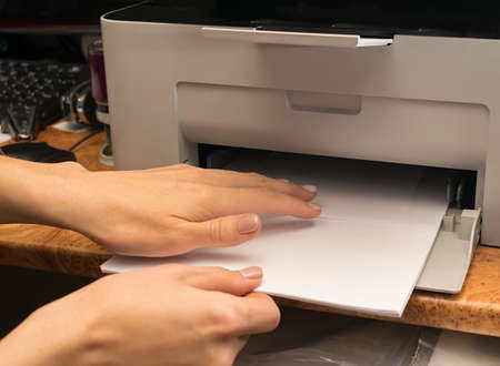 women hands in the office add paper inside the printer