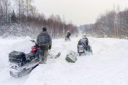 athletes on snowmobiles ride through snowdrifts on a snowy road Stok Fotoğraf