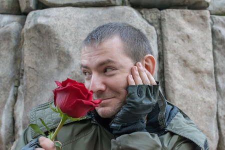 the guy looks coquettishly and sniffs a red rose flower