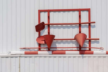 red fire shield on a white metal wall with buckets