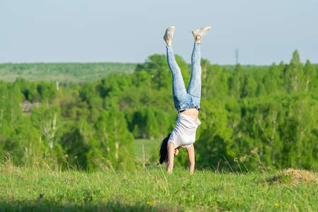 girl stands upside down in nature