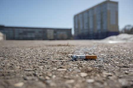 a Smoking abandoned cigarette butt lies on an asphalt pedestrian path on a city street